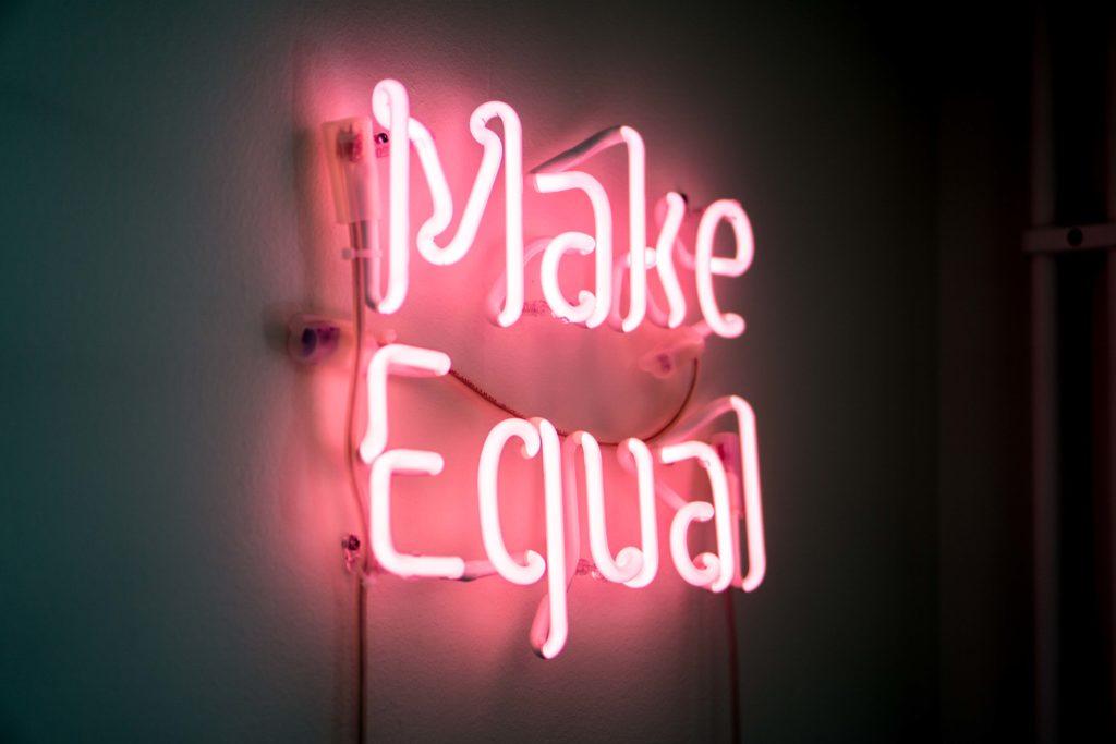 """Rosa neonskylt som bildar texten """"Make Equal""""."""